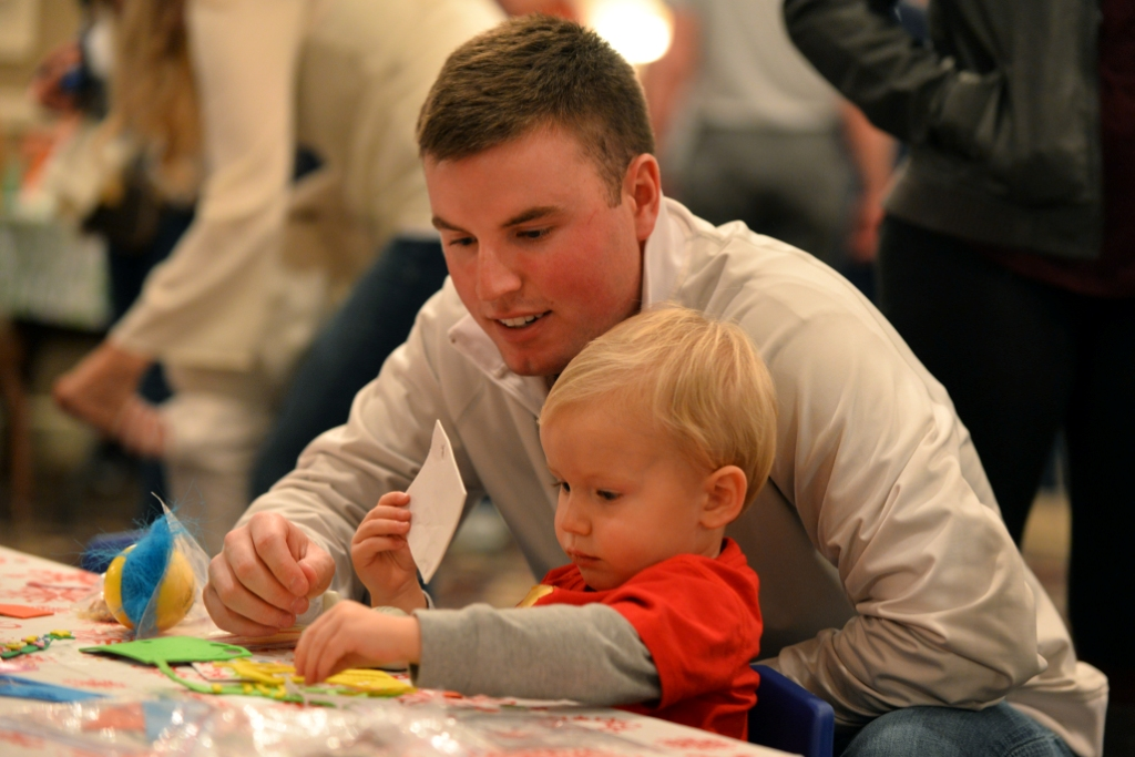 U.S. Air Force Airman 1st Class Kyle Gee, with the 55th Comptroller Squadron, decorated Christmas trees with his two-year-old son, Brady, at the Christmas Tree Celebration held at the Patriot Club on Dec. 3, Offutt Air Force Base, Neb. Hundreds of families attend the annual event. (U.S. Air Force photo by Josh Plueger/Released)